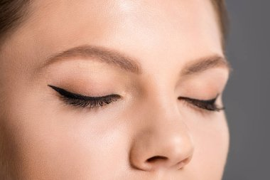 partial view of woman with black eyeliner on eyelids
