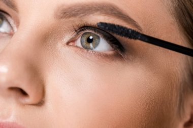 partial view of woman applying black mascara while looking away