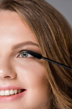 partial view of smiling woman and mascara brush