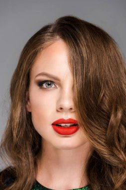 portrait of attractive young woman with red lipstick on lips looking at camera