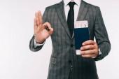 Fotografia immagine potata di uomo daffari che tiene passaporto e biglietto e mostrando bene gesto isolato su bianco