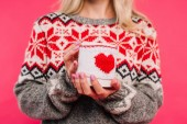 Fotografie cropped image of girl in sweater holding cup with heart sign isolated on pink