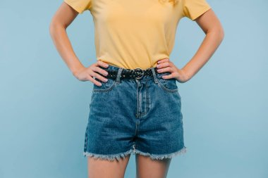 cropped image of girl in shirt and shorts standing with hands akimbo isolated on blue