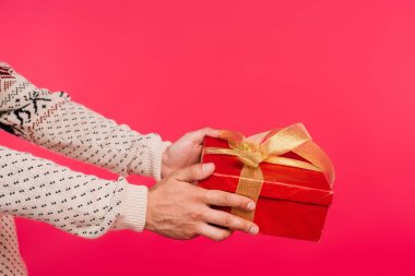 cropped image of man in sweater giving present isolated on pink