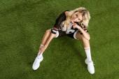 Fotografie přizpůsobit mladá žena v uniformě amerického fotbalu sedí na trávě a při pohledu na fotoaparát