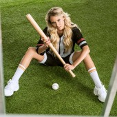 Fotografie high angle view of fit young woman in american football uniform with baseball bat sitting on grass and looking at camera