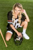 Fotografie high angle view of sporty young woman in american football uniform with helmet and baseball bat sitting on grass