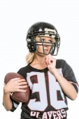 sporty young woman in american football uniform with ball isolated on white