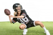 athletic young woman in american football uniform throwing ball while sitting squats on grass isolated on white