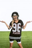 bewildered young woman in american football equipment gesturing isolated on white