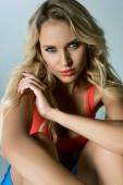 Fotografie attraktive sportliche junge Frau blickt in die Kamera auf grau
