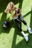 Photo overhead view of athletic young woman sitting on green grass with american football ball and helmet