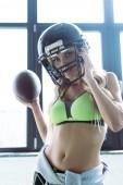Fotografie passen Sie junge Frau im Sport-BH und american-Football-Helm Besitz Ball und Blick in die Kamera