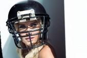 Fotografie close-up Portrait von junge Frau im Sport-BH und american-Football-Helm auf weiß