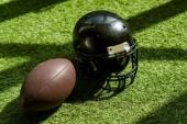 magas szög kilátás amerikai futball labda és a sisak a zöld fű