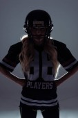 dark silhouette of sporty young woman in american football equipment on grey