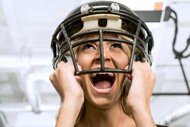 bottom view of mad young woman screaming and holding american football helmet on head