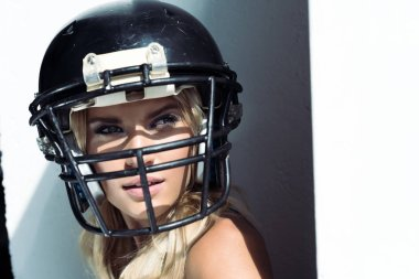 close-up portrait of young woman in sport bra and american football helmet on white