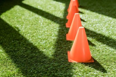 close-up shot of row of safety cones standing on green grass