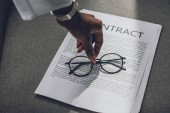 Fotografie cropped image of african american businesswoman putting glasses on contract in office