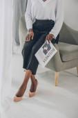 Fotografie oříznutý obraz stylová africká americká podnikatelka sedí na křesle a noviny v úřadu