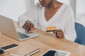 cropped image of african american businesswoman shopping online with laptop and credit card in office