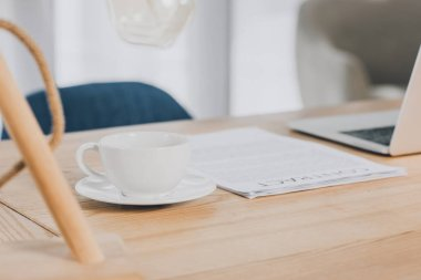 laptop, documents and cup of tea on wooden table in office