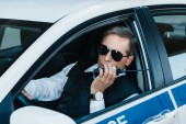 Photo middle aged male police officer in sunglasses talking on radio set in car