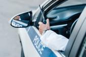 Fotografie ořízne obraz muž policista drží rádio v autě