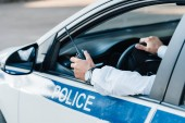ořízne obraz muž policista drží vysílačku v autě