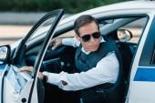 Fotografie vážnou středního věku muž policista neprůstřelnou vestu a sluneční brýle chůze ven z auta