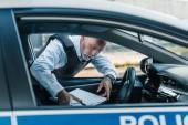 Reife Polizist in kugelsichere Weste Einnahme Zwischenablage von Auto auf der Straße