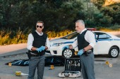 Fotografie mature policeman in latex gloves pointing by finger to colleague in sunglasses standing near at crime scene with corpse in body bag