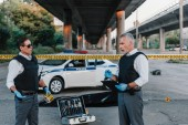 Fotografie mature policeman with clipboard talking to colleague in sunglasses near corpse in body bag at crime scene