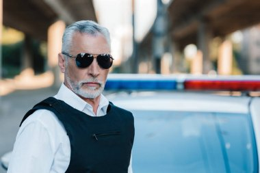 portrait of confident middle aged policeman in sunglasses and bulletproof vest near car at street