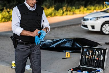 partial view of policeman with gun in holster putting on latex gloves at crime scene with corpse in body bag and case with investigation tools