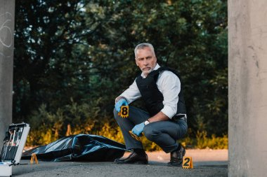 serious male police officer in latex gloves sitting at crime scene with corpse in body bag