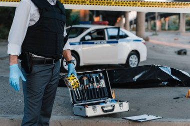 partial view of policeman in latex gloves holding police line at crime scene with corpse in body bag