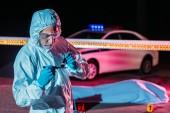 Fotografia concentrato il criminologo maschio maturo in vestito protettivo e guanti in lattice, prendendo le impronte digitali dal coltello alla scena del crimine