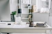 pen holder, cup of coffee and smartphone on table in light modern office