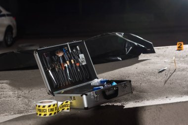 Close up view of case with investigation tools, police line and corpse in body bag at crime scene stock vector