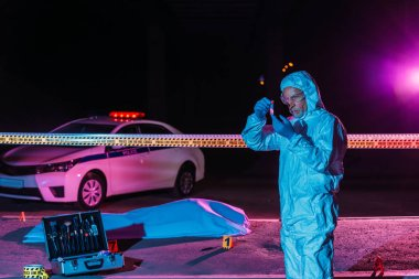 middle aged male criminologist in protective suit and latex gloves collecting evidence at crime scene with corpse