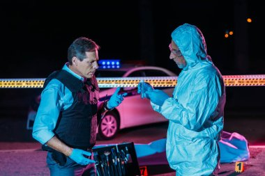 male criminologist in protecitve suit showing evidence to mature policeman at crime scene with corpse in body bag