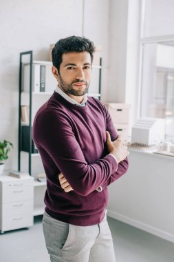 handsome designer in burgundy sweater standing with crossed arms and looking at camera in office