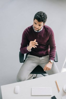 high angle view of pensive handsome designer in burgundy sweater sitting at table in office