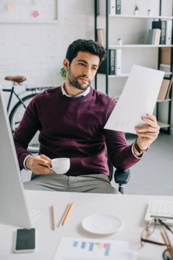 handsome businessman in burgundy sweater holding cup of coffee and reading documents in office