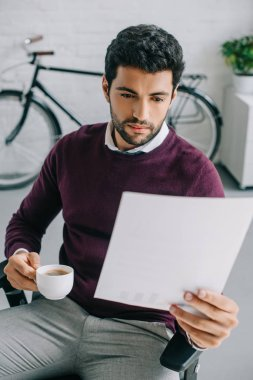 designer with bristle holding cup of coffee and reading documents in office
