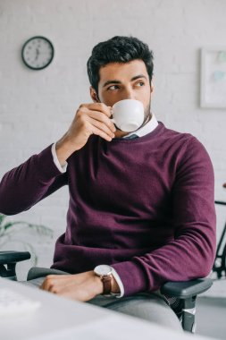 handsome designer in burgundy sweater drinking coffee in office