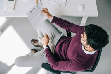 high angle view of designer in burgundy sweater reading contract in office