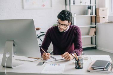 handsome designer in burgundy sweater writing something to notebook in office